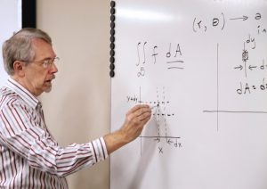 Robert Moore writing mathematical equations on a whiteboard