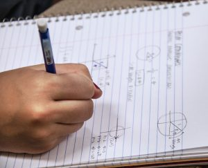 hand writing math equations in a notebook